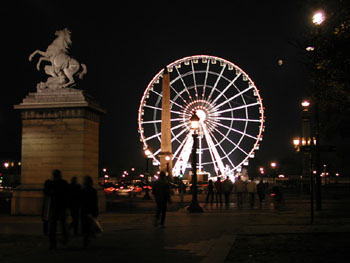 Ferris wheel with onlooking statue.